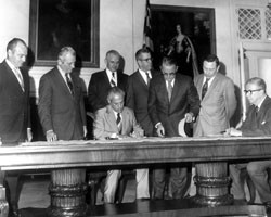 An old, black and white photo of seven men standing behind another man that is seated at the table, signing a document.