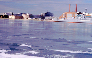 An image of an icy river. A large military ship is in the background.