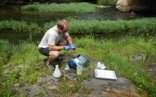 A man crouches next to a stream surrounded by scientific equipment. He has blue plastic gloves on.
