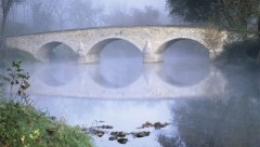 A picture of a bridge across a river. It is slightly foggy. It is a stone bridge with three arches.