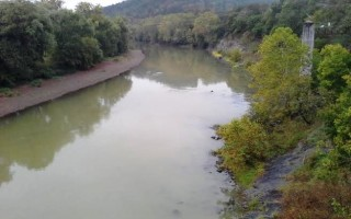 Photo of a muddy-looking river from the top of a bridge.