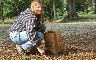 A woman crouching, putting acorns into a paper bag.
