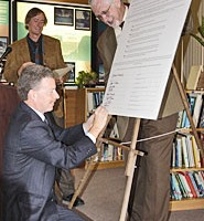 A man kneeling down to sign a large sheet of paper.
