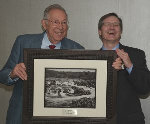Two men standing behind a print of the Potomac.