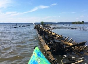 Kayak alongside a sunken ship barely sticking out of the water at Mallows Bay