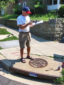 Man standing on a storm drain