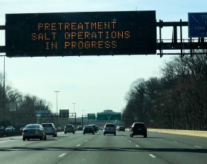 Cars driving on a freeway below a sign that reads: Pretreatment Salt Operations in Progress
