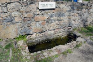 "A stone bathtub built in the ground with a stone wall behind it. A plaque on the wall says ""George Washington's Bathtub (1748)"""