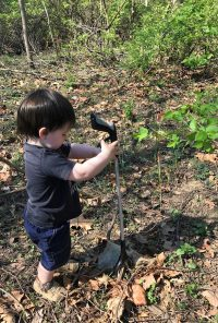 A small boy picks up trash off a forest floor.