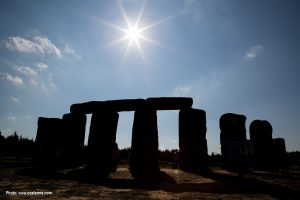 Several large blocks of foam backlit by the sun. They are arranged to look like Stonehenge.