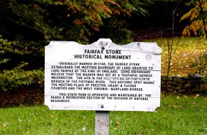 A white, aged plaque that tells the story of Fairfax Stone.