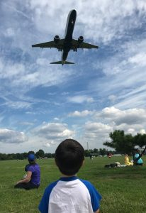 A little boy watches a large plane fly directly overhead.