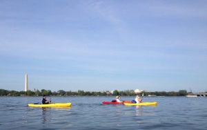 Three kayakers in the Potomac river in front of D.C. monuments