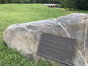 "A large rock with a plaque that says, ""Monocacy Aqueduct: Preserved for Future Generations. Rededicated May 2005."""