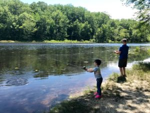 A boy and his father are fishing in a pond at Cedarville State Park.