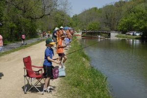 Children with fishing rods lined up along the side of a canal.