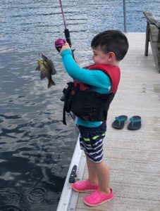 A little boy is holding up a fishing pole with a fish on the hook.