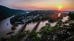 An aerial view of Harpers Ferry, WV. Two rivers converge with a town in the background.