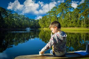 Little boy sitting on a bench reaching for bait. A lake is in the background.