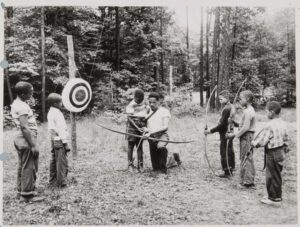 Young black boys receiving an archery lesson.