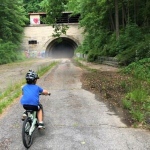 Boy riding into an abandoned tunnel. Lush vegetation on both sides of the trail.