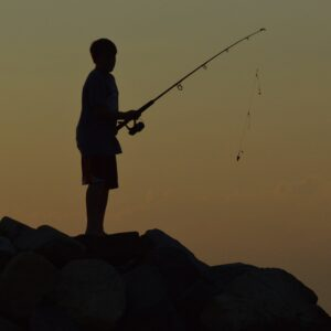 Silhouette of a young boy fishing at sunset.